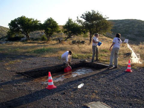 Fig. 4: Bailing out Trench A after heavy rain, Alexis Belis, Allisa Stoimenoff and Heather Kelly.