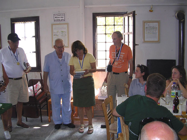 Fig. 16: Mary Voyatzis, center, receiving awards from Nikos Kostopoulos, near left, on occasion of visit of Mr. and Mrs. Nicholas Karabots, far left. David Romano, right.