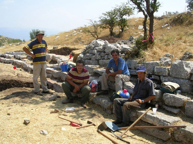 Fig. 16: Greek workmen Thanassis Christeas, Giannis Markolephas, Giorgos Aglamisis, and Ilias Aivalis taking a break on the steps in front of the stoa.