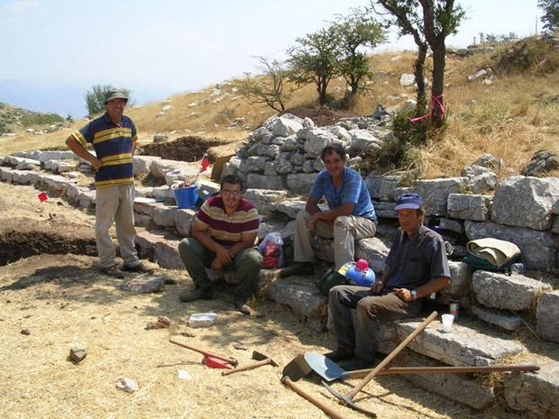 Fig. 16: Greek workmen Thanassis Christeas, Giannis Markolephas, Giorgos Aglamisis, and Ilias Aivalis taking a break on the steps in front of the stoa.