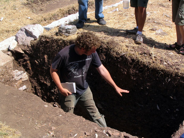 Fig. 17: Jared Benton discussing stratigraphy in Trench G, below the steps.